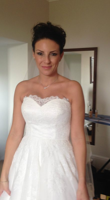 Bride in white dress in wedding hair and makeup.
