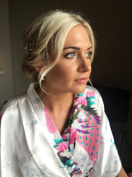 A female showcasing styled hair and a face of makeup on her wedding day