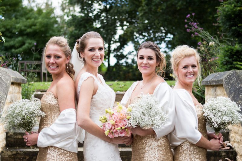 Cotswolds bride and bridesmaids in Wedding Hair and Makeup standing outside back to back holding bouquets.