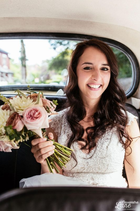 Cheshire bride in hair and makeup smiling in a car. She is wearing a white dress and is holding a bouquet.