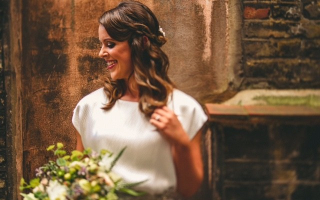 Brunette kent bride in Wedding Hair and Makeup smiling and looking to the right. holding bouquet and wearing white dress.