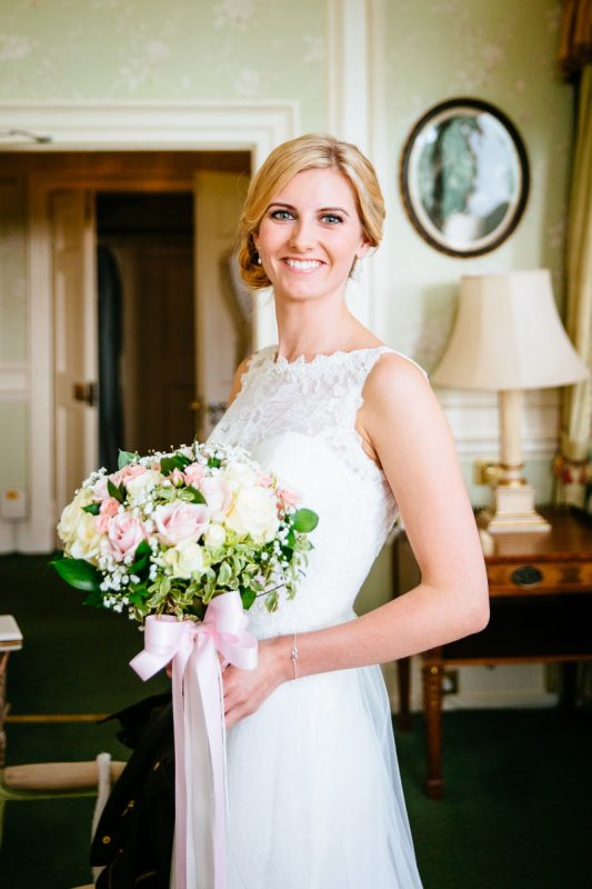 Kent bride in Wedding Hair and Makeup smiling at camera indoors in white dress, holding bouquet.
