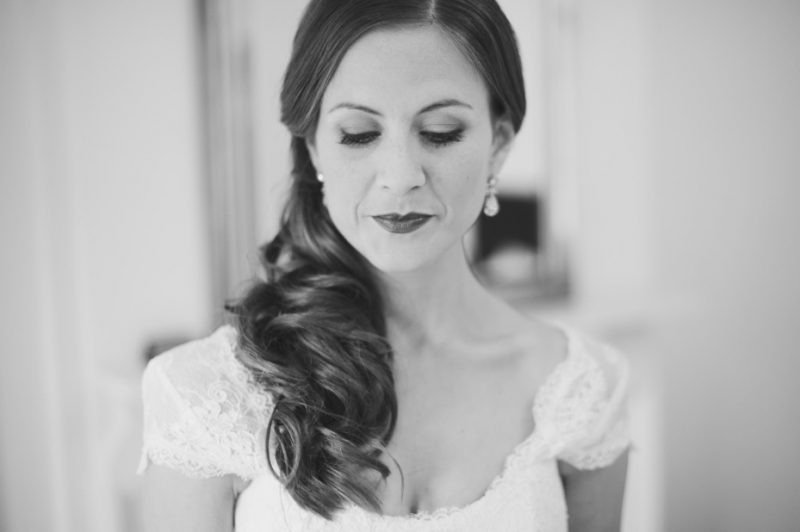 Bride in Wedding Hair and Makeup looking down in black and white.