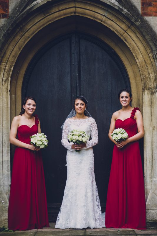 Bride and two bridesmaids standing outside church in Gloucestershire.