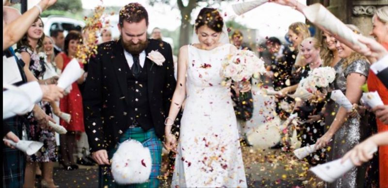 Guidlford bride and groom showered in confetti in full hair and makeup.
