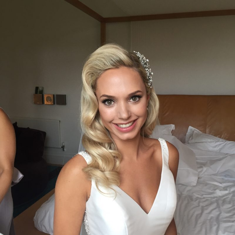 a bride with her hair styled and makeup applied getting ready on her wedding day