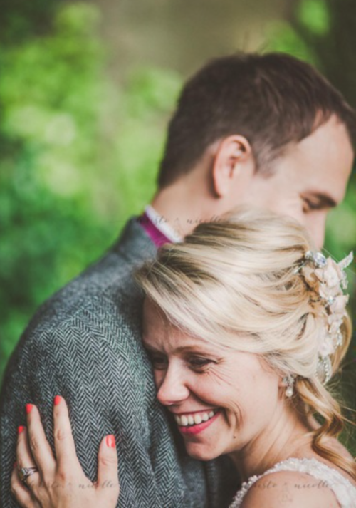 Guildford bride in hair and makeup embracing groom and smiling.
