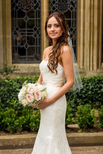 London Bride outside holding a bouquet in hair and makeup.