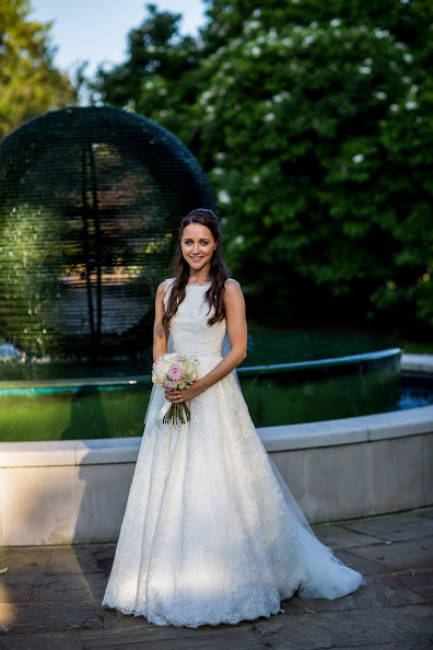 London bride stood by a fountain in hair and makeup.