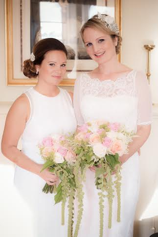 Two kent brides in Wedding Hair and Makeup standing next to each other in white dresses holding pink bouquets.