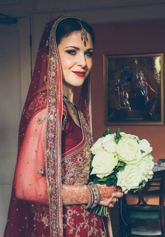 kent bride in Wedding Hair and Makeup holding white bouquet in a red sari.