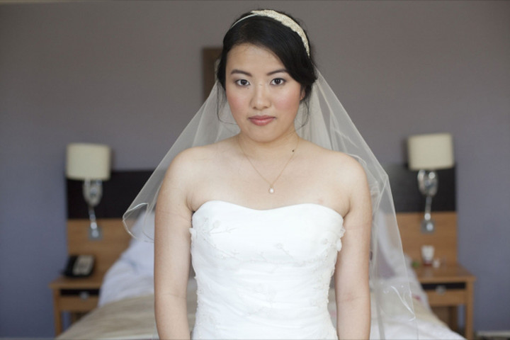 oriental bride wearing wedding makeup on her wedding day