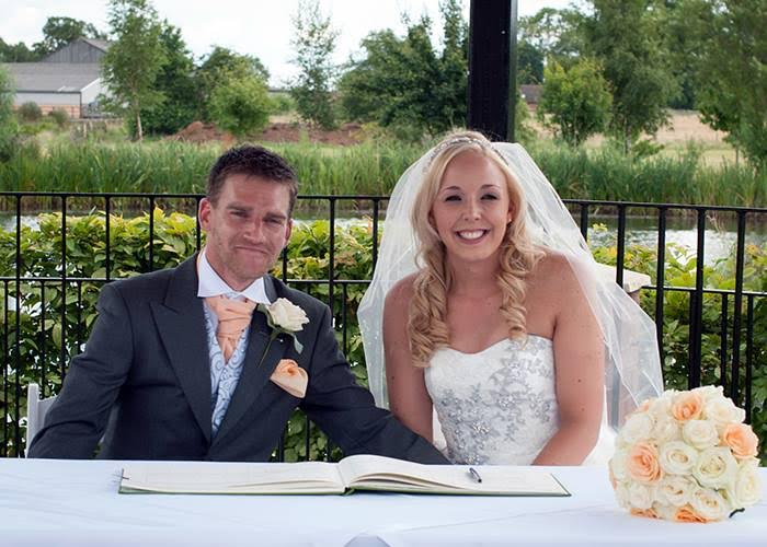 Cotswolds bride in wedding hair and makeup smiling next to groom outside.