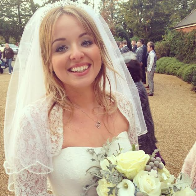 Cotswolds bride smiling outside in wedding makeup, veil and bouquet.