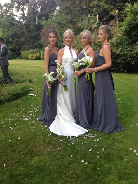 cotswold bride and bridesmaids posing outside in hair and makeup.