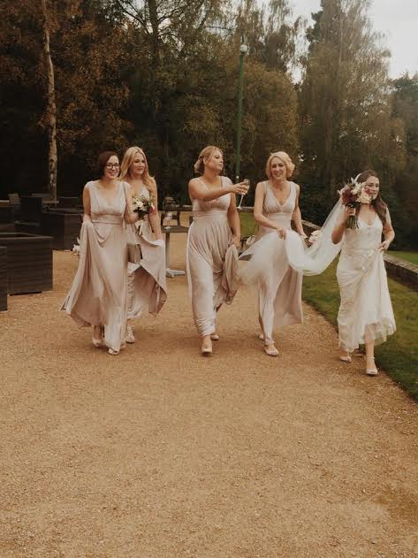 Cotswolds bride and bridesmaids running down a path in hair and makeup.