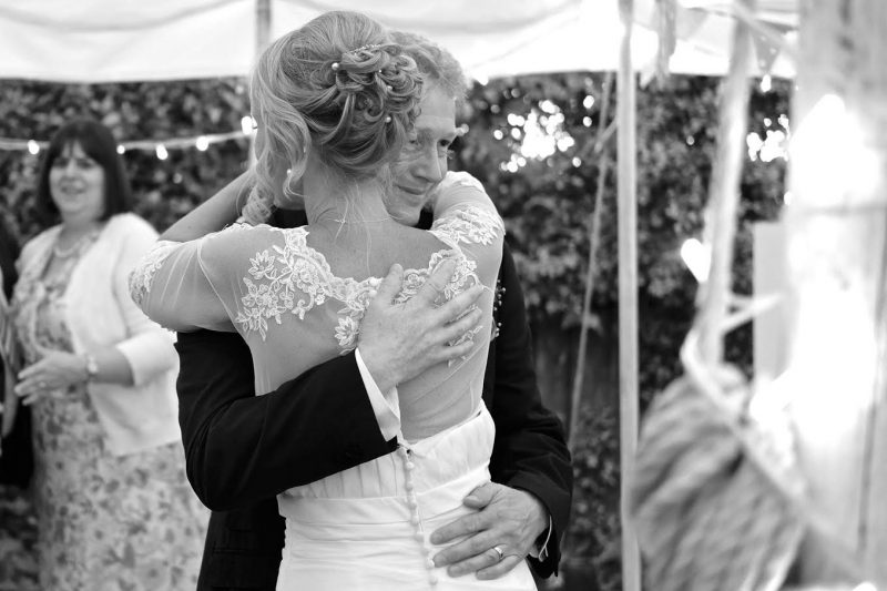 a bride embraces her groom as they dance together on their wedding day