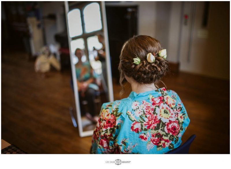 view of the back of the bride hair styles with her face reflected in the mirror