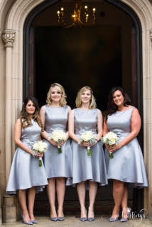 four bridesmaids stand outside a church