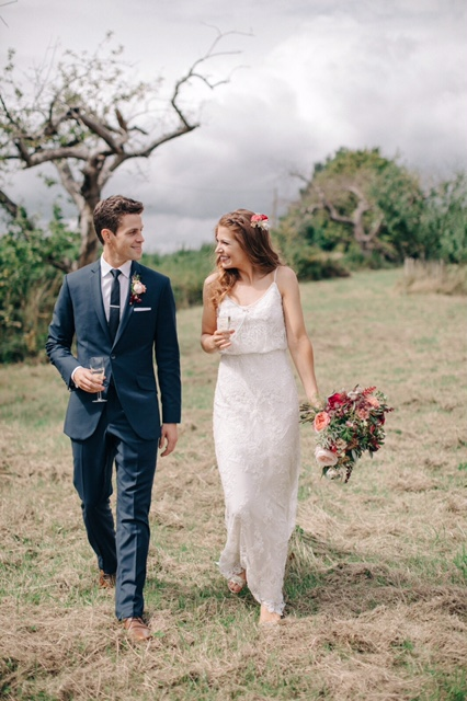 bride and groom smile at each other as they walk through a field on wedding day