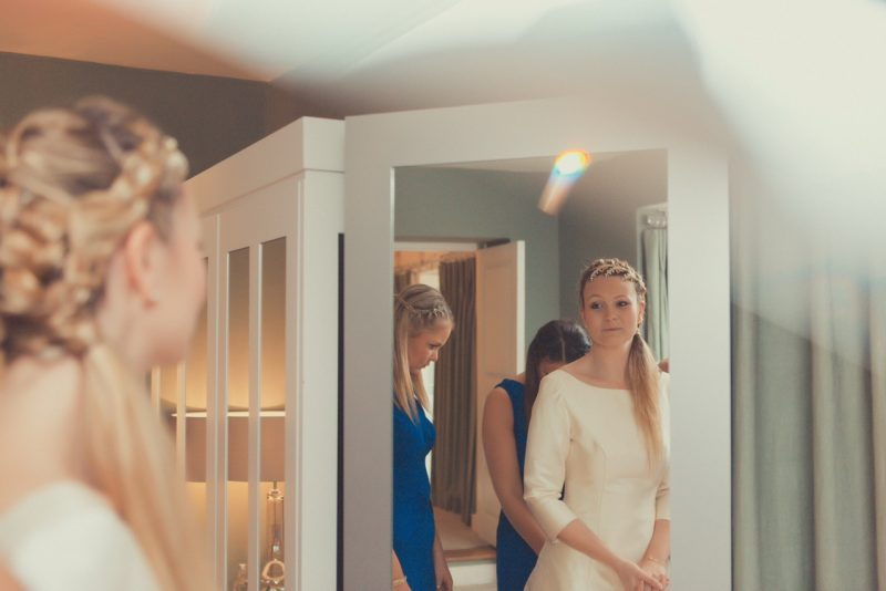 cotswold bride looking in mirror in Wedding Hair and Makeup.