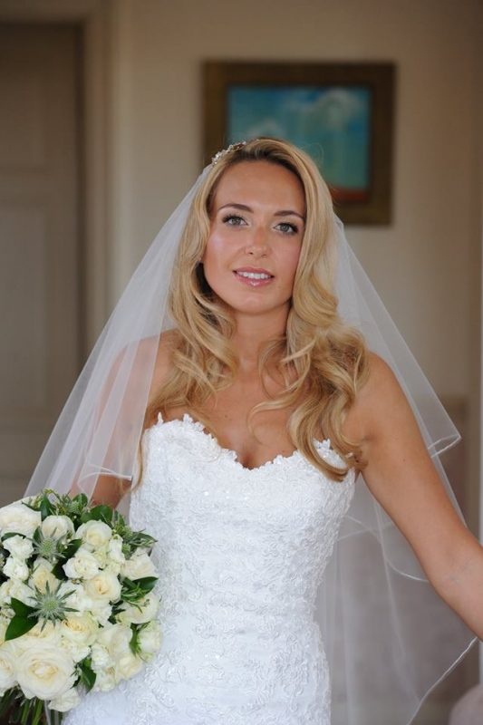 Blonde bride in wedding hair and makeup, she is in a white dress, veil and is holding a bouquet.