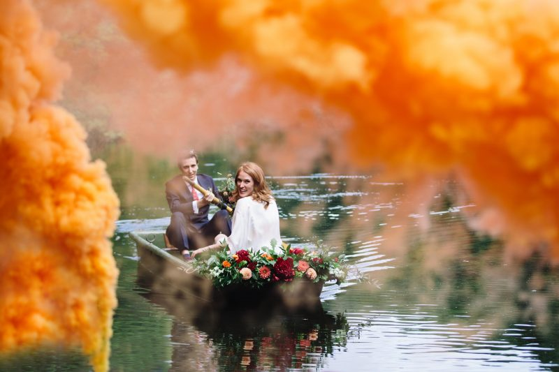 bride smiles over her shoulder from a small rowing boat as she glides upstream with her groom