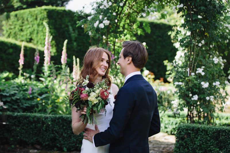 bride gazes in her groom eyes holding her bouquet