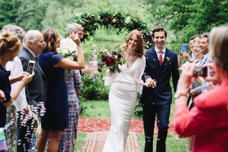 Bride with her wedding hair and makeup walking up the aisle with her groom and confetti in the air
