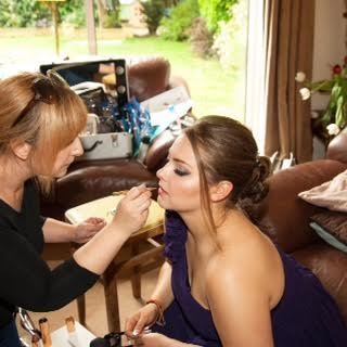 A makeup artist applying lipstick to a ladies face