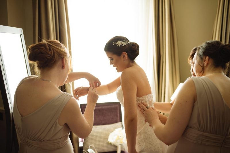 oriental bride with hair in an up do and makeup on getting into her wedding dress