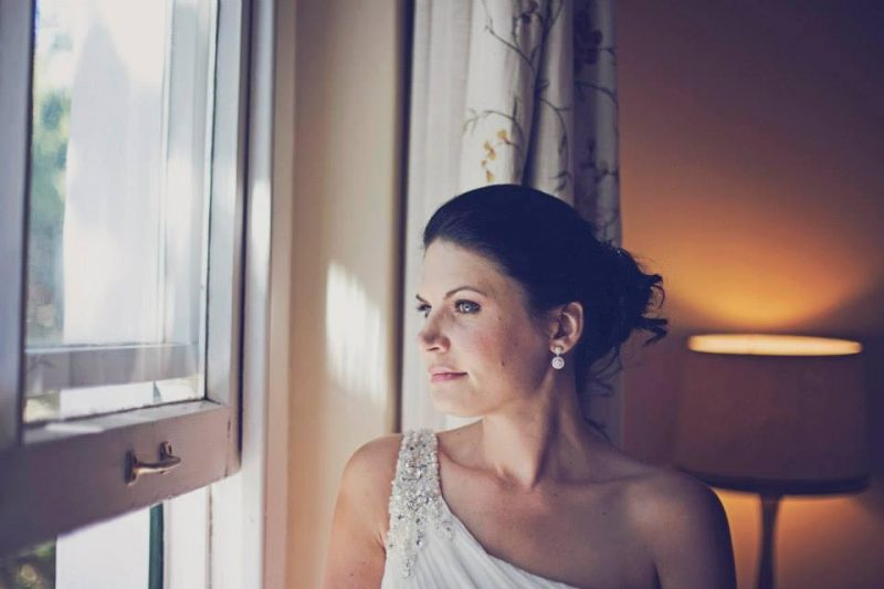 London Bride looking out of window in hair and makeup.