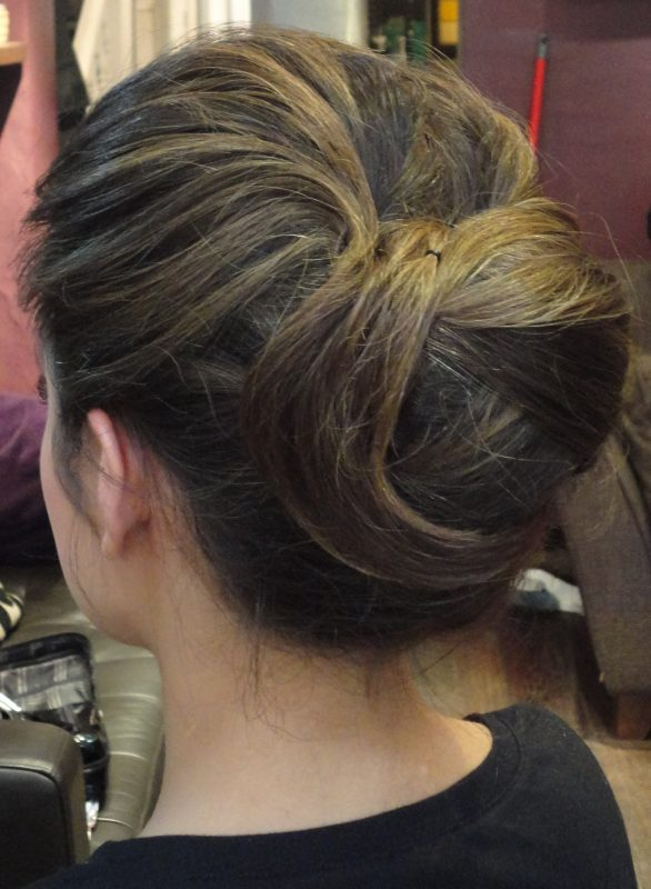 female showcases the back of her head styled in an up do by a hair stylist in South West France