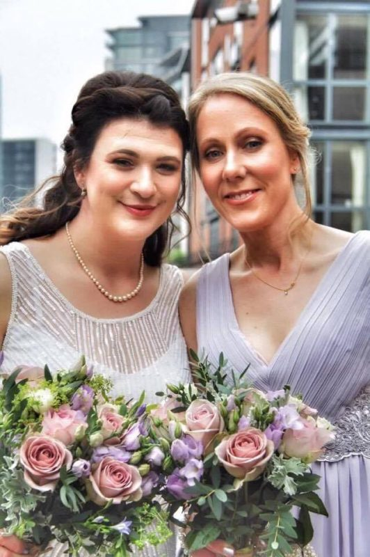 a bride and her bridesmaid smile holding their bouquet with makeup by Solihull Makeup Artist