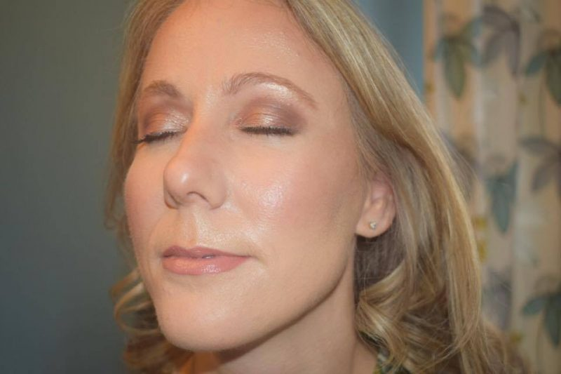 A lady faces the light and closes her eyes to showcase her face of makeup by Solihull Makeup Artist