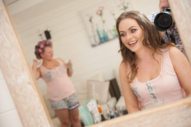A bride smiles into the mirror showcasing her makeup by Solihull Makeup Artist