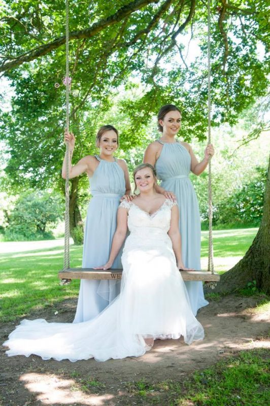 A bride poses with her bridesmaids with makeup by Solihull Makeup Artist