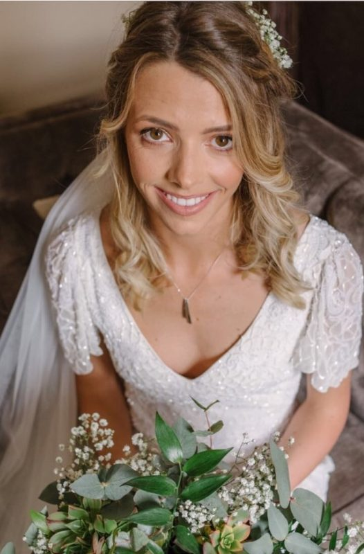 a blonde female bride showcases her wedding makeup