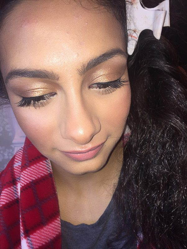 a young female looks down and showcases her false eyelashes and eye makeup