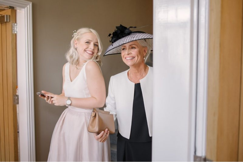 a blonde bride poses with the mother of the bride wearing a hat