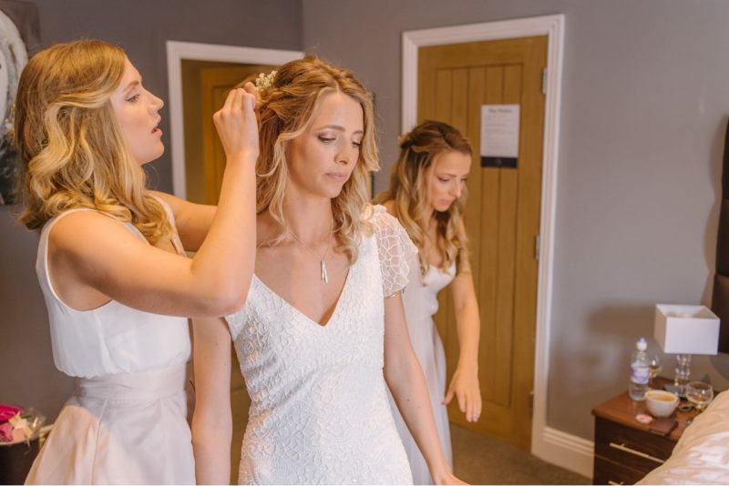 a blonde female bride stands in her wedding dress as she has her hair adjusted