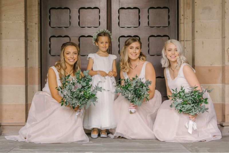 A trio of bridesmaids and a flower girl each holding a bouquet of flowers pose in front of a doorway