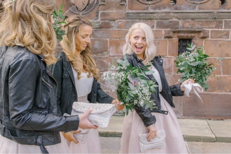 a group of bridesmaids waling in line holding their bouquets all wearing pastel pink dresses and black leather jackets
