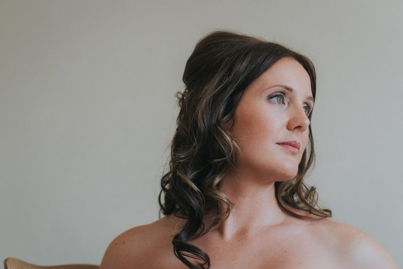 A bride showcases her face of makeup on her wedding day y west midland makeup artist